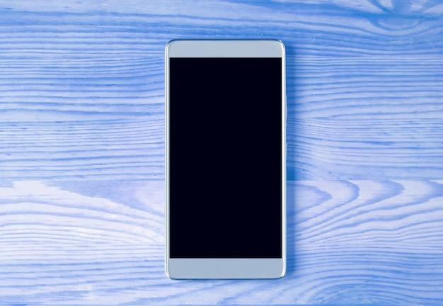 Vue de dessus d'un smartphone argenté isolé sur une table en bois de couleur bleue avec espace libre