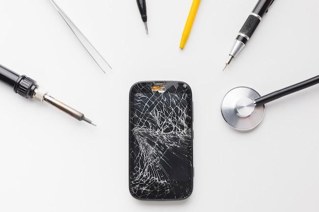Vue de dessus d'un smartphone cassé avec des outils de réparation