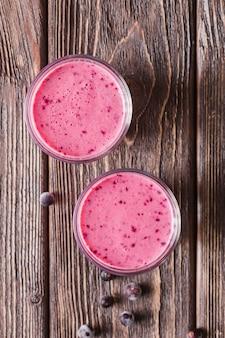 Vue de dessus smoothie rose dans des verres aux bleuets