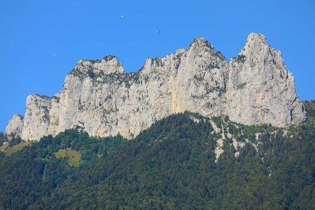 Vue de dessus des sommets des montagnes avec ciel bleu et parachutes en été
