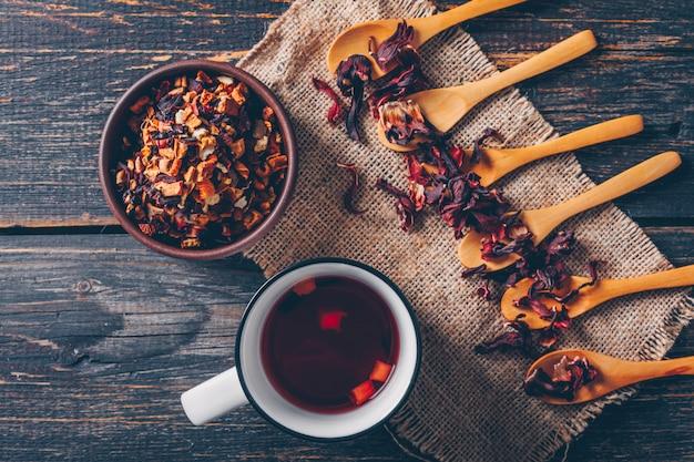 Vue de dessus une sorte de thé dans un bol et des cuillères avec une tasse de thé sur un tissu de sac et un fond en bois foncé. horizontal