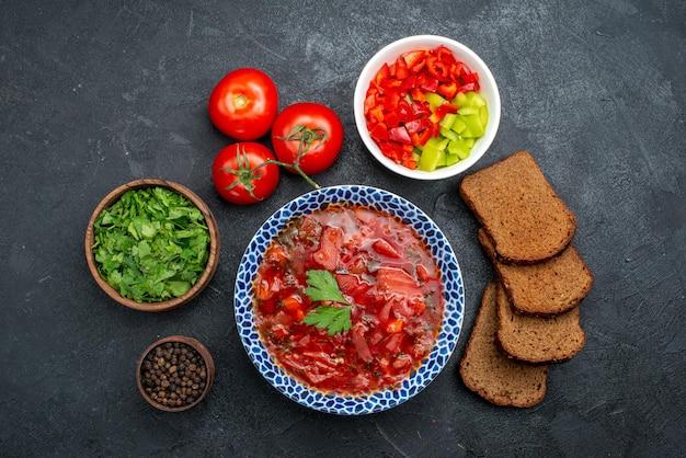 Vue de dessus de la soupe au bortsch avec des miches de pain noir et des légumes verts sur un espace sombre