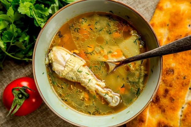 Vue de dessus soupe au poulet servie avec tomates et pain aux herbes
