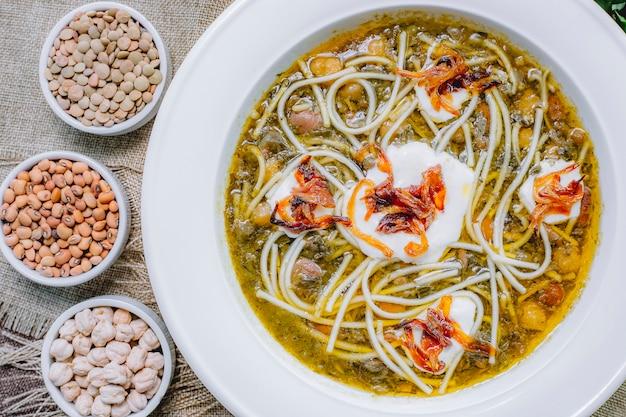Vue de dessus soupe aux haricots avec nouilles aux oignons grillés crème sure et haricots