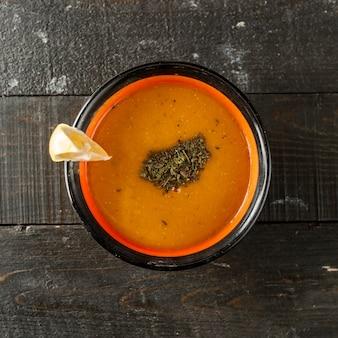 Vue de dessus de la soupe aux lentilles garnie de feuilles de menthe séchées et de citron