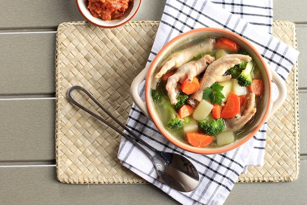 Vue de dessus soupe aux pieds de poulet (griffe) clair aux légumes avec pommes de terre, brocoli et carottes. servi sur une table en bois gris dans un bol marron avec du sambal