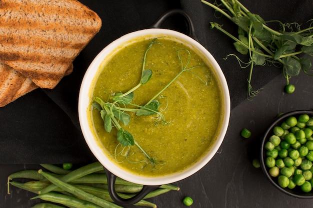 Vue de dessus de la soupe aux pois d'hiver dans un bol avec du pain grillé