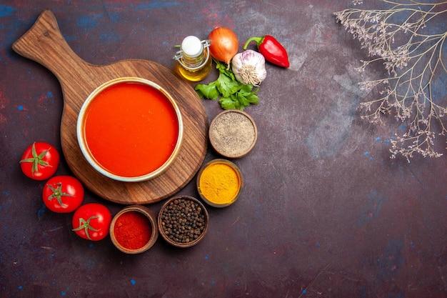 Vue de dessus de la soupe aux tomates avec assaisonnements sur fond noir