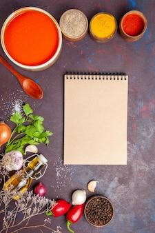 Vue de dessus de la soupe aux tomates cuites à partir de tomates fraîches avec différents assaisonnements sur tableau noir
