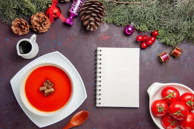 Vue de dessus de la soupe aux tomates avec du pain tranché à l'intérieur sur fond noir