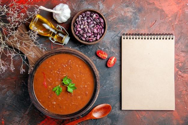 Vue de dessus de la soupe aux tomates sur une planche à découper brune et ordinateur portable sur une table de couleurs mélangées