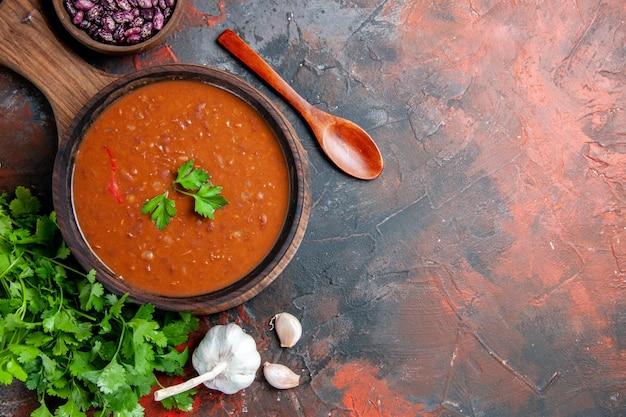 Vue de dessus de la soupe aux tomates sur une planche à découper brune sur une table de couleurs mélangées
