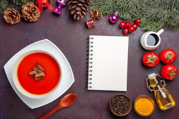 Vue de dessus de la soupe aux tomates avec tomates fraîches et assaisonnements sur tableau noir
