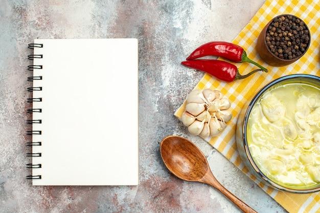 Vue de dessus de la soupe de boulettes de dushbara dans un bol de piments à l'ail cuillère en bois avec une serviette de cuisine au poivre noir