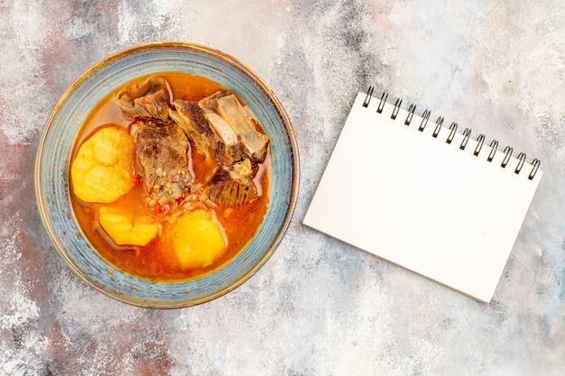 Vue de dessus de la soupe bozbash un cahier sur fond nu