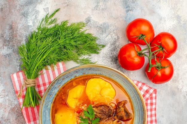 Vue de dessus de la soupe bozbash avec un tas de tomates à l'aneth sur fond nude