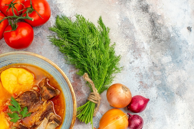 Vue de dessus de la soupe bozbash un tas de tomates à l'aneth oignons sur fond nu