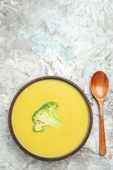 Vue de dessus de la soupe de brocoli crémeuse dans un bol brun et cuillère sur des images de table gris