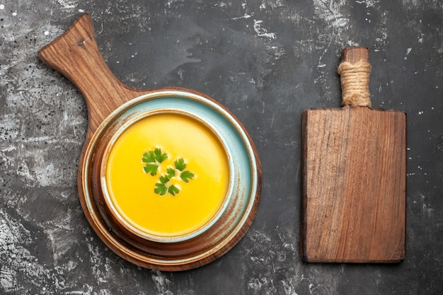 Vue de dessus de la soupe à la citrouille à l'intérieur de la plaque sur fond sombre