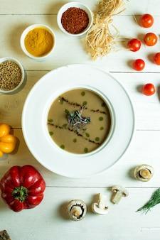 Vue de dessus de la soupe à la crème de champignons dans un bol blanc