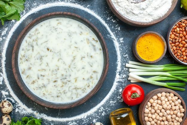 Vue de dessus soupe dovga dans un bol en bois bouteille d'huile de persil oignon vert bol de pois sur table