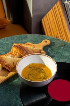 Une vue de dessus de la soupe à l'intérieur de la plaque avec du pain sur la table de la soupe