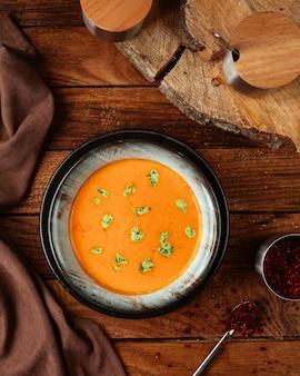 Une vue de dessus soupe à l'orange avec des feuilles sur le repas de nourriture de bureau en bois