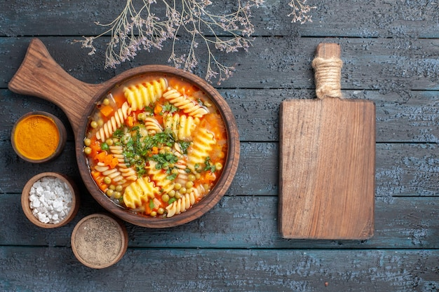 Vue de dessus soupe de pâtes en spirale délicieux repas avec différents assaisonnements sur une soupe de bureau bleu foncé couleur plat de pâtes italiennes cuisine