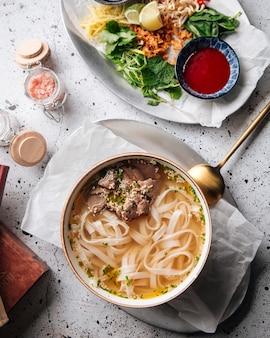 Vue de dessus sur la soupe pho bo vietnamienne avec des nouilles de boeuf et de riz sur la table servie