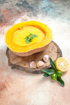 Vue de dessus de la soupe de potiron aux herbes et ail sur la planche de citron