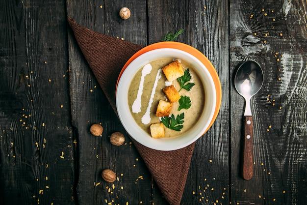 Vue de dessus sur la soupe de purée saine appétissante sur la serviette sur la table en bois