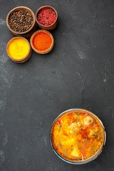 Vue de dessus soupe savoureuse avec différents assaisonnements sur le bureau gris soupe repas nourriture assaisonnement de viande épicé