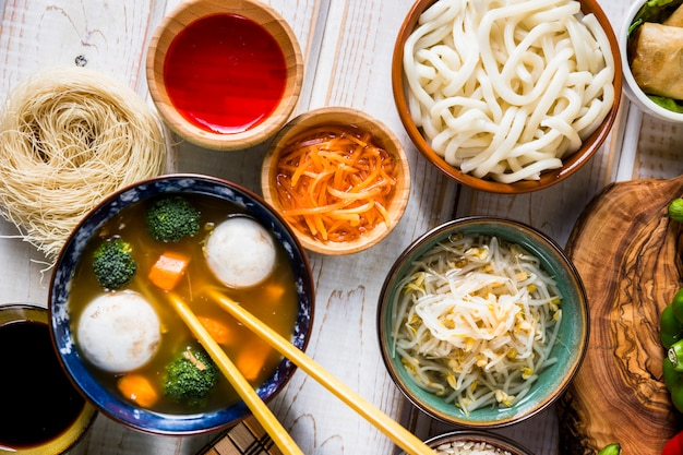 Une vue de dessus de la soupe thaïlandaise de poisson et de légumes avec des nouilles udon; germes de sauce et de haricots sur le bureau blanc