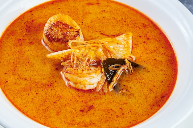 Vue de dessus sur la soupe tom yum servie dans une assiette blanche avec du riz