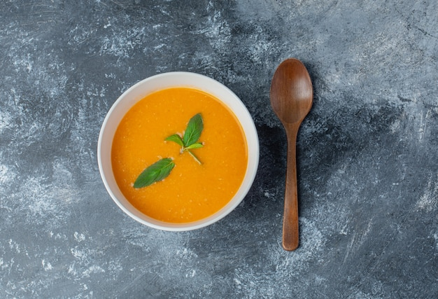 Vue de dessus de la soupe de tomates fraîches et d'une cuillère en bois.