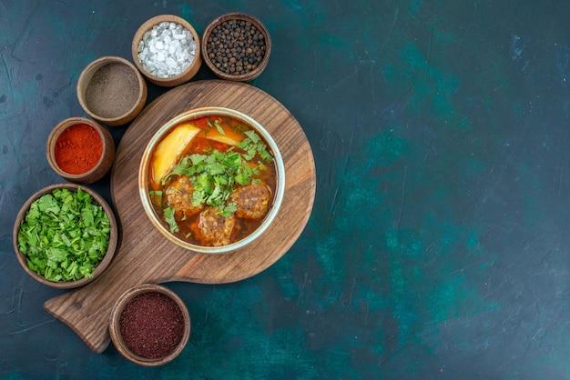 Vue de dessus de la soupe à la viande avec des boulettes de viande vertes et des pommes de terre tranchées sur le bureau bleu foncé