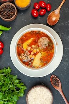 Vue de dessus d'une soupe de viande délicieuse avec des légumes verts et des assaisonnements sur fond sombre