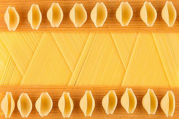 Vue de dessus de spaghetti italien de types longs avec fond comme fond de pâtes décoratives