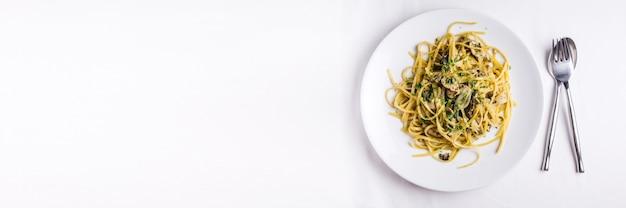 Vue de dessus des spaghettis aux huîtres servis dans une assiette blanche sur une nappe blanche. avec espace copie