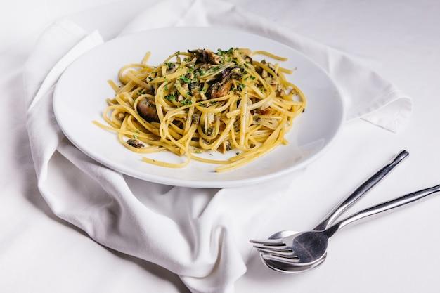 Vue de dessus des spaghettis aux huîtres servis dans une assiette blanche sur une nappe blanche.