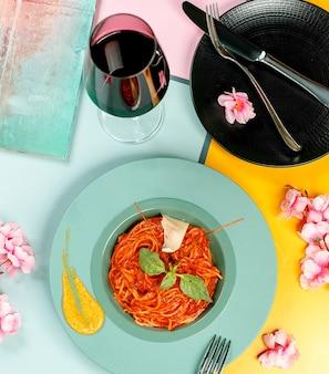Vue de dessus des spaghettis bolognais surmontés de basilic dans une assiette turquoise