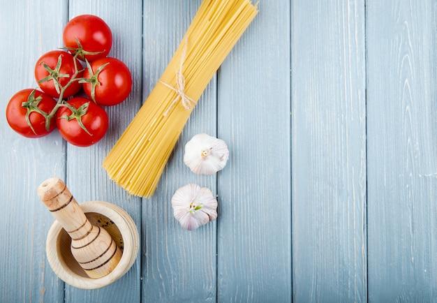 Vue de dessus des spaghettis crus attachés avec une corde avec de l'ail de tomates fraîches et du mortier en bois avec copie espace sur fond rustique
