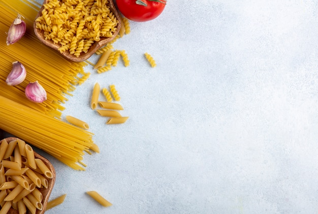 Vue de dessus des spaghettis crus avec des pâtes crues dans des bols avec de l'ail et des tomates sur une surface grise