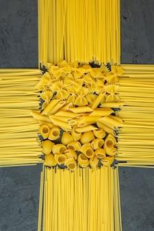 Vue de dessus des spaghettis crus avec des pâtes sèches penne et farfalle sur fond noir