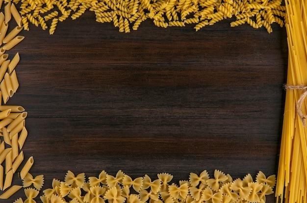 Vue de dessus des spaghettis crus avec des pâtes sur une surface en bois