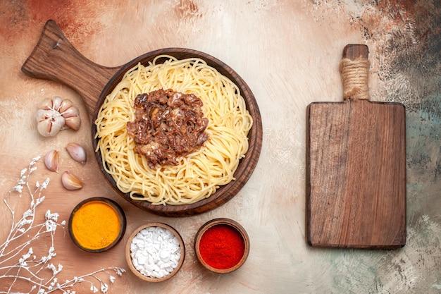 Vue de dessus des spaghettis cuits avec de la viande hachée sur un assaisonnement pour pâtes de bureau en bois