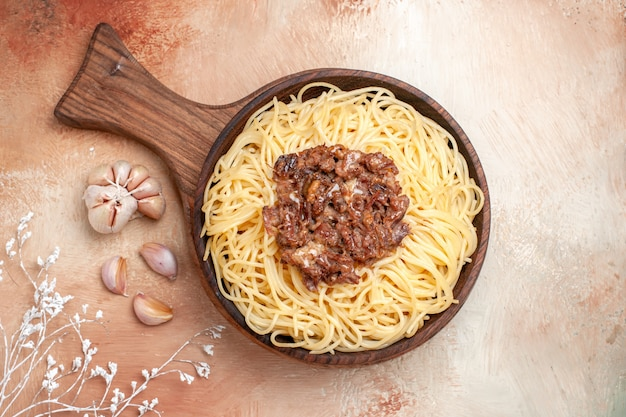 Vue de dessus des spaghettis cuits avec de la viande hachée sur des assaisonnements de plat de pâte de pâtes au sol en bois