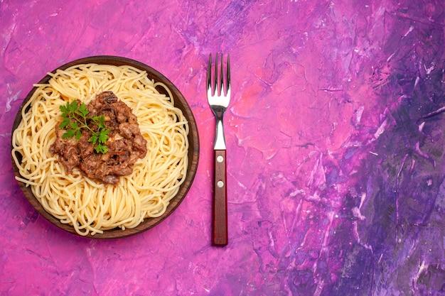 Vue de dessus des spaghettis cuits avec de la viande hachée sur des pâtes de pâte à plat de couleur rose clair
