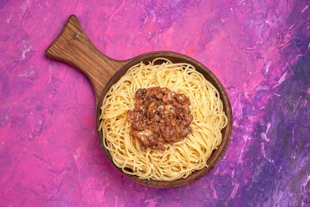 Vue de dessus des spaghettis cuits avec de la viande hachée sur un plat de pâte de table rose assaisonnement pour pâtes