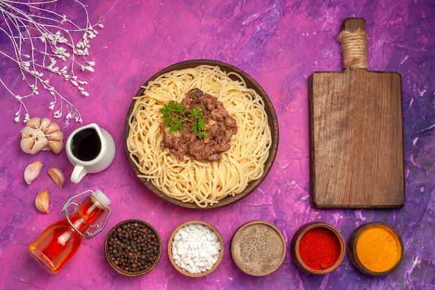 Vue de dessus des spaghettis cuits avec de la viande hachée sur un plat de pâtes à la pâte d'assaisonnement de bureau rose